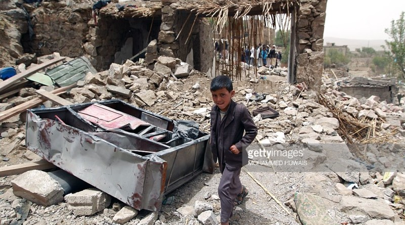 A Yemeni boy walks past the rubble of destroyed houses in the village of Bani Matar, 70 kilometers (43 miles) West of Sanaa, on April 4, 2015, a day after it was reportedly hit by an airstrike by the Saudi-led coalition against Shiite Huthi rebel positions. A Saudi-led coalition pounded rebels in southern Yemen and dropped more arms to loyalist fighters as the UN Security Council prepared to discuss calls for 'humanitarian pauses' in the air war. AFP PHOTO / MOHAMMED HUWAIS